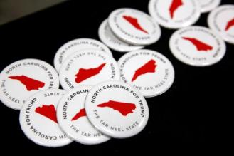 North Carolina campaign buttons sit on a table before the start of a rally with Trump in Fletcher, North Carolina