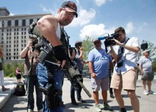 Steve Thacker with a rifle and a handgun is surrounded by members of the news media in Cleveland's public square in Cleveland